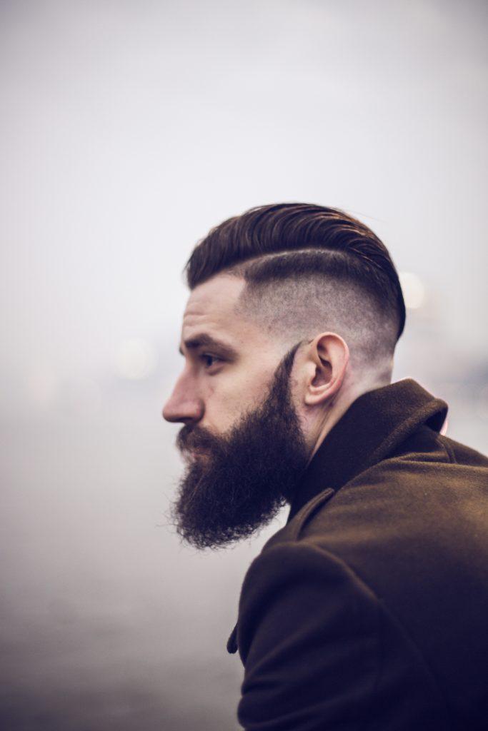 Hombre de barba y corte de cabello de lado