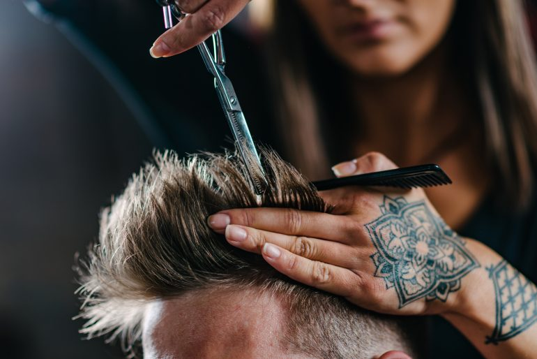 Mujer cortando el cabello a un hombre
