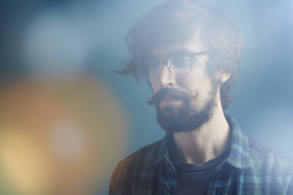 joven con barba, bigote y lentes