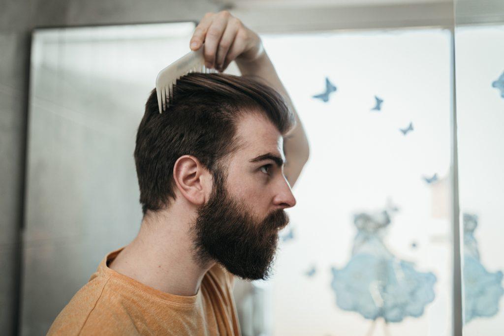 Hombre de cabello lacio peinándose