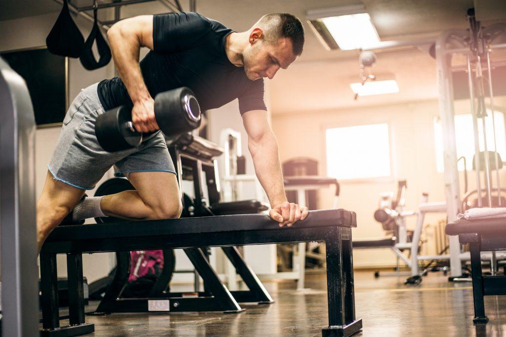 hombre haciendo remo arrodillado en gimnasio