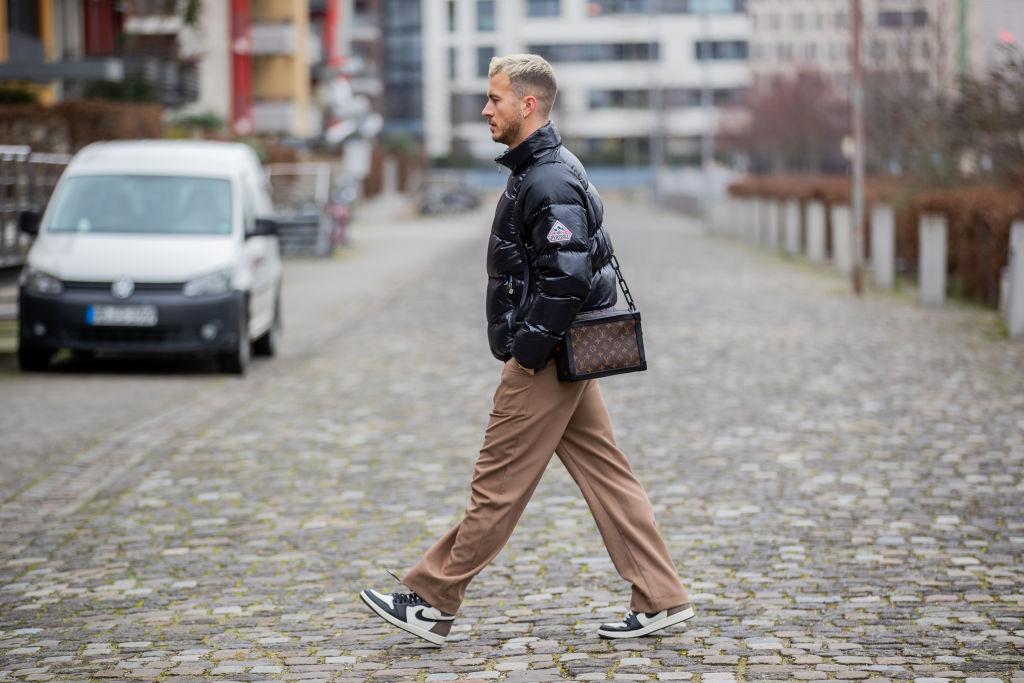 Hombre joven caminando en la calle con tenis Jordan
